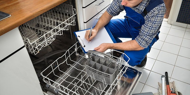Young technician checking dishwasher and noting on paper