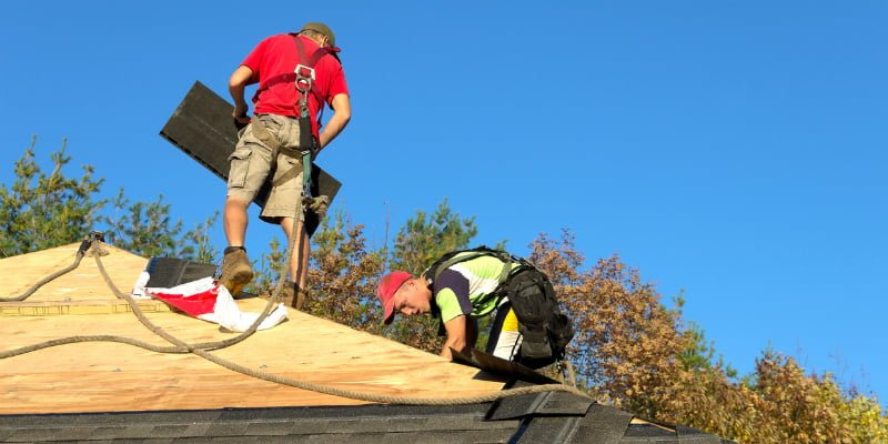 Roof repairs, two workers changing roof layer with safety belts
