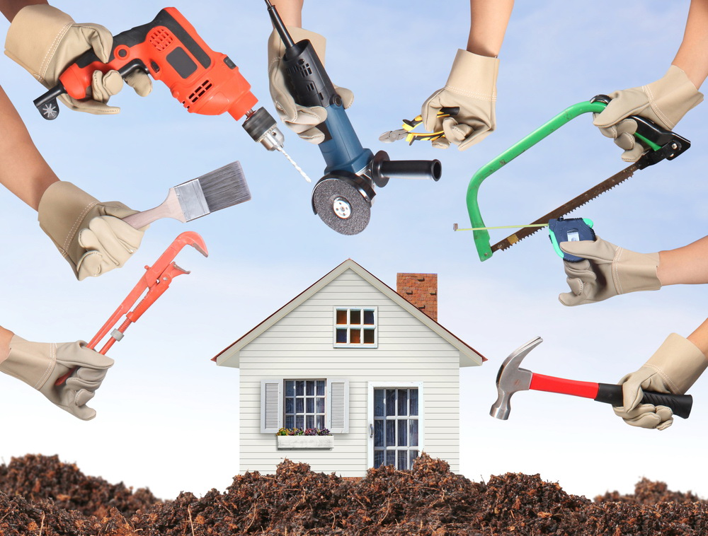 Group of people hands around a home with many home maintainence tools