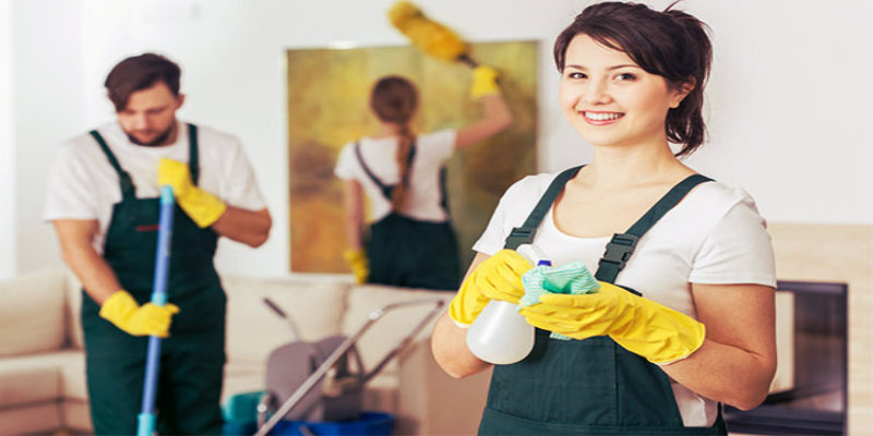 Team of three cleaning workers cleaning a home with cleaning products